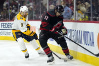 Nashville Predators left wing Filip Forsberg (9) and Carolina Hurricanes left wing Warren Foegele (13) chase the puck during the second period in Game 1 of an NHL hockey Stanley Cup first-round playoff series in Raleigh, N.C., Monday, May 17, 2021. (AP Photo/Gerry Broome)