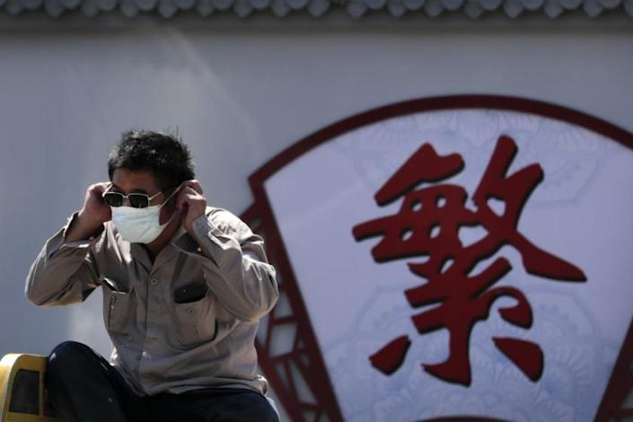 "A man puts on his face mask to protect against the coronavirus in Beijing on Tuesday as he passes by the Chinese character for ""complicated."" <span class=""copyright"">(Andy Wong / Associated Press)</span>"