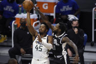 Utah Jazz guard Donovan Mitchell, left, shoots while pressured by Los Angeles Clippers guard Patrick Beverley during the first half of an NBA basketball game in Los Angeles, Friday, Feb. 19, 2021. (AP Photo/Kelvin Kuo)
