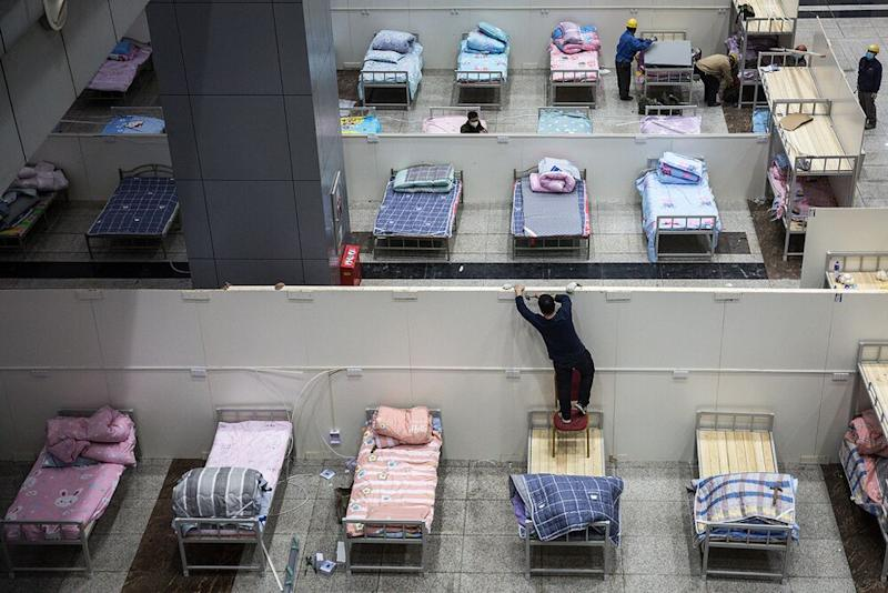 Workers in Wuhan, China, set up beds in a quarantine center | Photo by Getty Images
