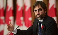 Heritage Minister Steven Guilbeault speaks with a row of Canadian flags behind him.