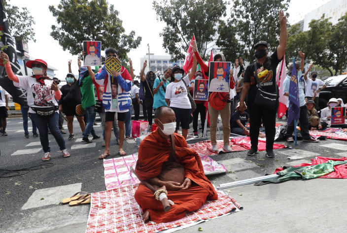 Buddhist monk and pro-democracy activists protest outside the Attorney General office in Bangkok, Thailand, Monday, March 8, 2021. Prosecutors in Thailand charged 18 pro-democracy activists Monday with sedition while lodging additional charges against three of them for defaming the monarchy during protests in September last year. (AP Photo/Sakchai Lalit)