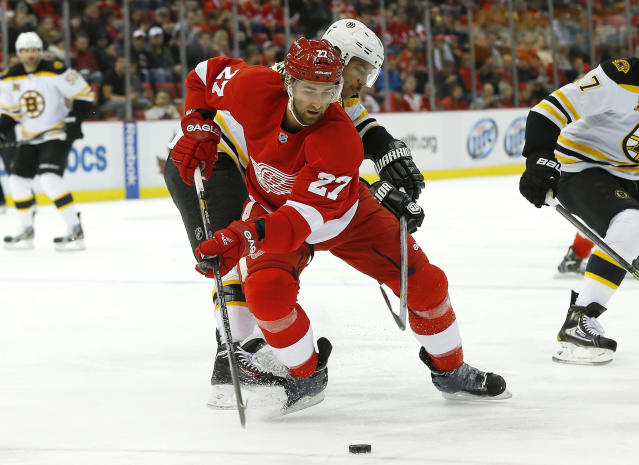 Detroit Red Wings defenseman Kyle Quincey (27) keeps the puck from Boston Bruins right wing Jarome Iginla (12) in the first period of an NHL hockey game in Detroit, Wednesday, Nov. 27, 2013. (AP Photo/Paul Sancya)