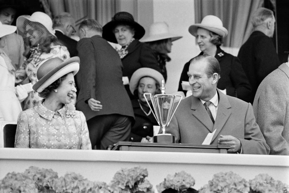 The couple share a laugh in May 1972 as they attend a horse race at Longchamp racecourse, outside Paris, during their five-day official visit in France. (Photo credit should read STAFF/AFP via Getty Images)