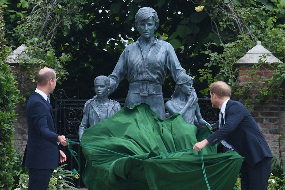 TOPSHOT - Britain's Prince William, Duke of Cambridge (L) and Britain's Prince Harry, Duke of Sussex unveil a statue of their mother, Princess Diana at The Sunken Garden in Kensington Palace, London on July 1, 2021, which would have been her 60th birthday. - Princes William and Harry set aside their differences on Thursday to unveil a new statue of their mother, Princess Diana, on what would have been her 60th birthday. (Photo by Dominic Lipinski / POOL / AFP) (Photo by DOMINIC LIPINSKI/POOL/AFP via Getty Images)