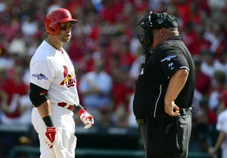Oct 4, 2013; St. Louis, MO, USA; St. Louis Cardinals right fielder Carlos Beltran (left) argues with home plate umpire Wally Bell (right) after striking out looking in the sixth inning in game two of the National League divisional series playoff baseball game against the Pittsburgh Pirates at Busch Stadium. Jeff Curry-USA TODAY Sports