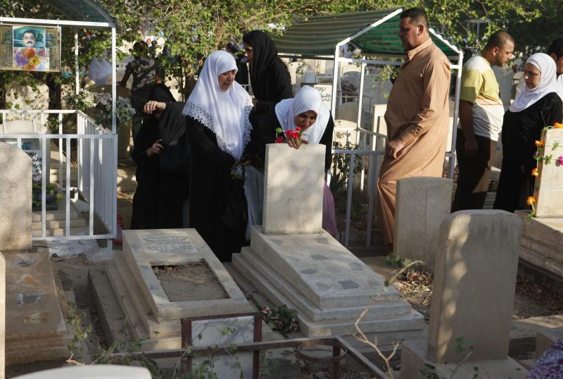 People visit a cemetery during the first day of Eid al-Fitr in the Azamiyah area of north Baghdad, Iraq, Sunday, Aug. 19, 2012. The three-day Eid al-Fitr holiday marks the end of the holy fasting month of Ramadan. (AP Photo/Karim Kadim)