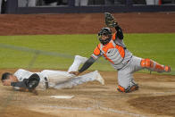 Baltimore Orioles catcher Pedro Severino holds up his glove with the ball in it after tagging out New York Yankees' Gio Urshela during the 11th inning of a baseball game Wednesday, April 7, 2021, at Yankee Stadium in New York. (AP Photo/Kathy Willens)