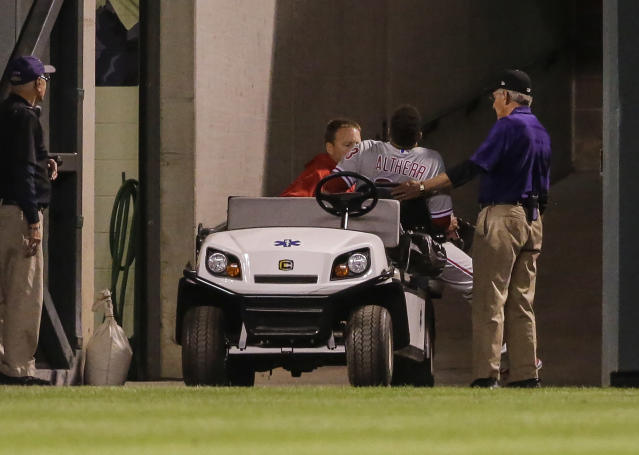 Philadelphia Phillies left fielder Aaron Altherr is taken off the field by a trainer after injuring himself on the wall during the fourth inning of a baseball game against the Colorado Rockies on Monday, Sept. 24, 2018, in Denver. (AP PhotoJack Dempsey)