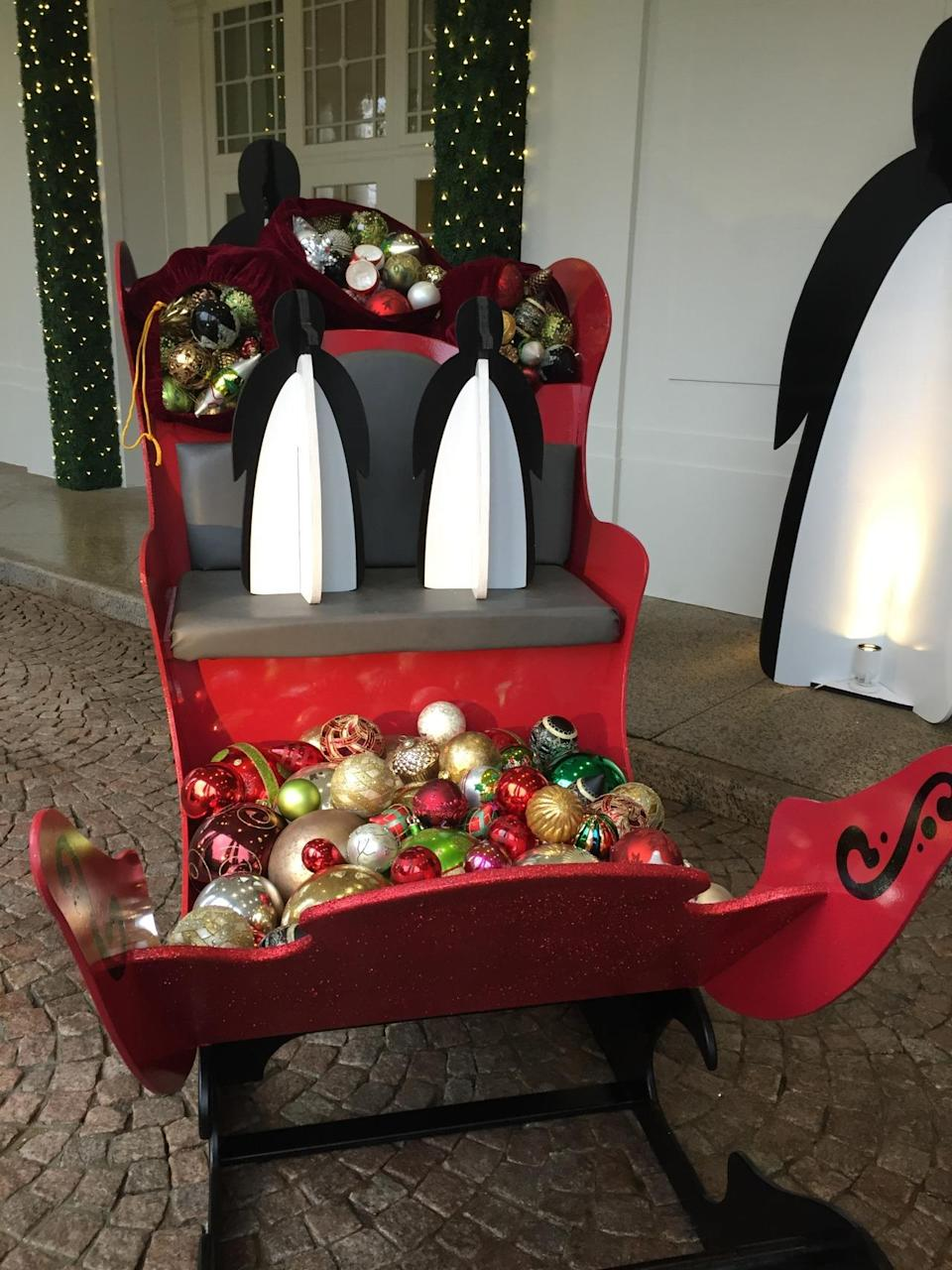 <p>Guests to the White House are greeted by massive wooden penguins and a penguin-driven sleigh full of ornaments outside the East Wing entrance. (Photo: Cassie Carothers)</p>