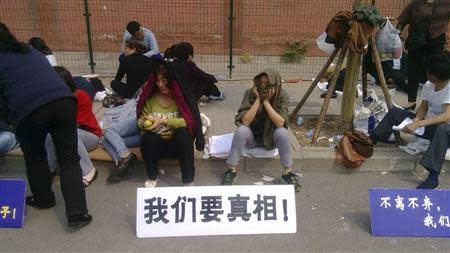 """Family members of passengers aboard the missing Malaysia Airlines flight MH370 gather during a sit-in protest outside the Malaysian embassy in Beijing, April 25, 2014. The sign in white reads, """"We want the truth"""". REUTERS/Courtesy of family members/Handout via Reuters"""