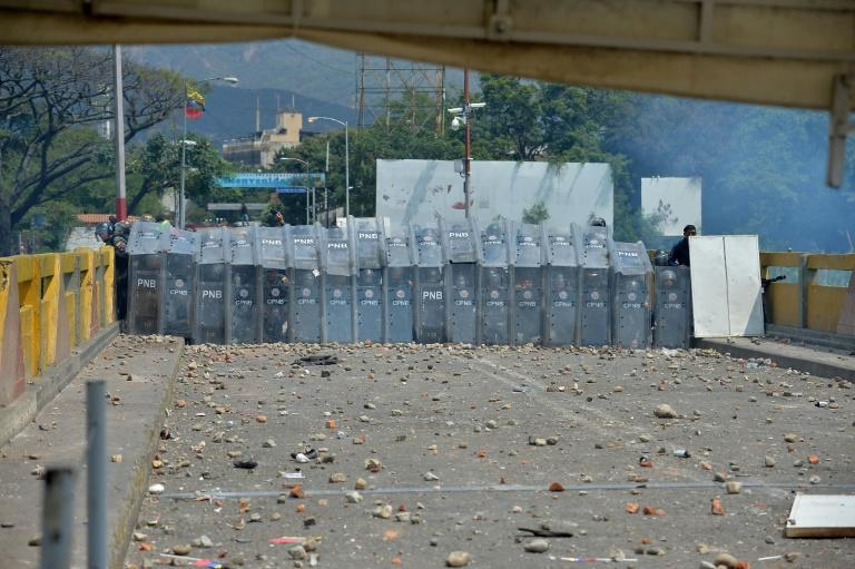 Venezuelan police sought protection behind their shields from a hail of rocks thrown by protesters at the Simon Bolivar international bridge across from Cucuta, Colombia