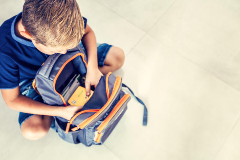 Boy checks the school backpack