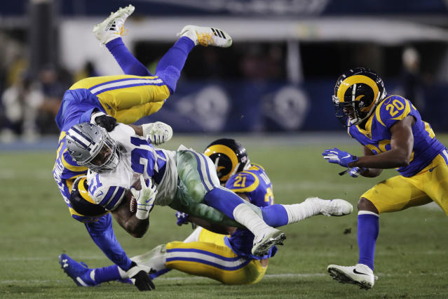 Ezekiel Elliott is tackled by a group of Rams in Saturday's divisional round playoff game. (AP)