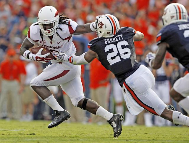 Arkansas running back Alex Collins (3) stiff arms Auburn linebacker Justin Garrett (26) as he tries to get around him during the second half of an NCAA college football game on Saturday, Aug. 30, 2014, in Auburn, Ala. (AP Photo/Butch Dill)