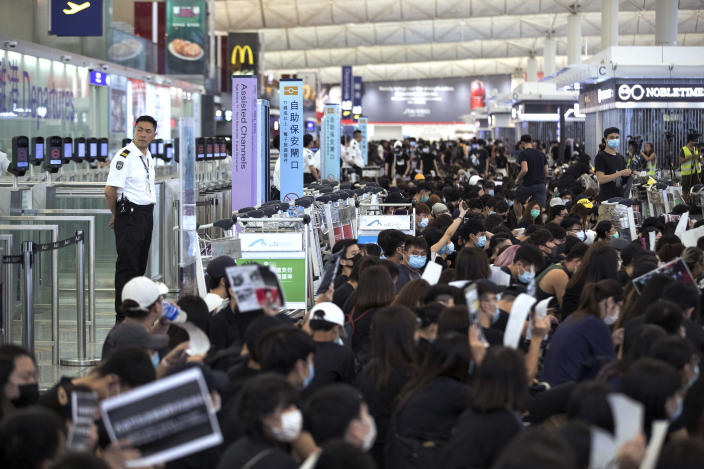 Airport security personnel look on as protesters using luggage trolleys to block the departure gates during a demonstration at the Airport in Hong Kong, Tuesday, Aug. 13, 2019. (Photo: Vincent Yu/AP)