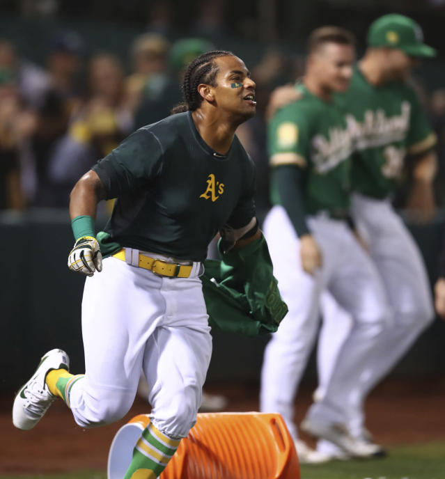 Oakland Athletics' Khris Davis, left, celebrates after hitting a walk-off home run in the 10th inning of a baseball game against the Minnesota Twins on Friday, Sept. 21, 2018, in Oakland, Calif. (AP Photo/Ben Margot)