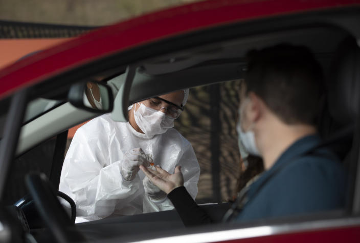 A health worker collects a sample from a person at a drive-thru test site for COVID-19 amid the new coronavirus pandemic in Niteroi, Brazil, Wednesday, June 3, 2020. (AP Photo/Silvia Izquierdo)