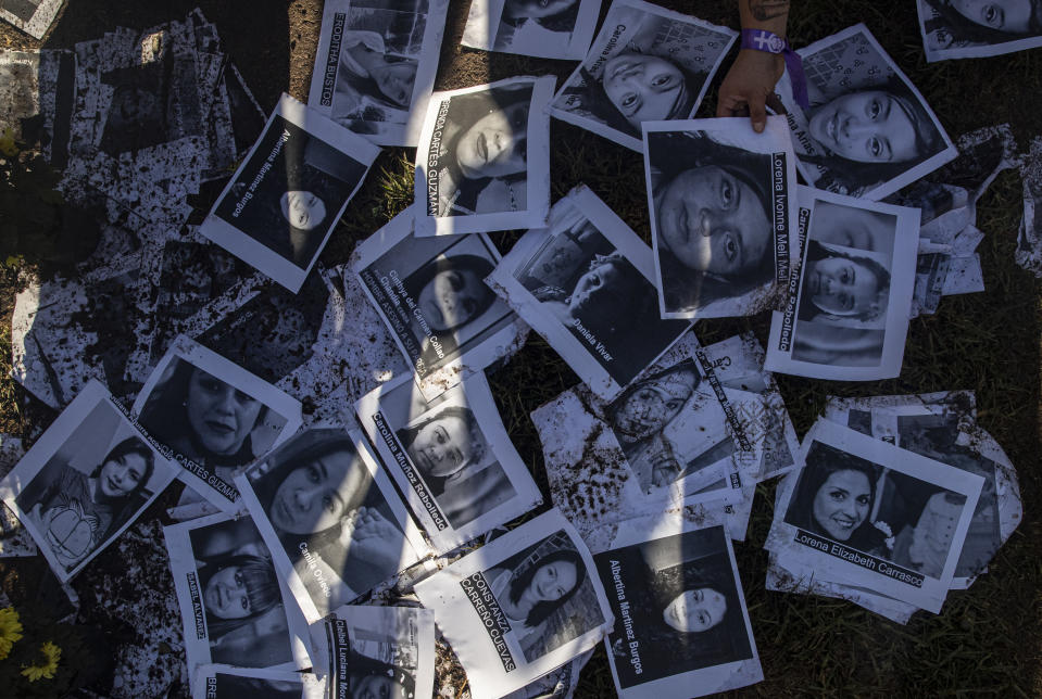 A woman places images of female victims of gender violence on the wet ground during a protest commemorating International Women's Day in Santiago, Chile, on Monday, March 8, 2021. (AP Photo/Esteban Félix)