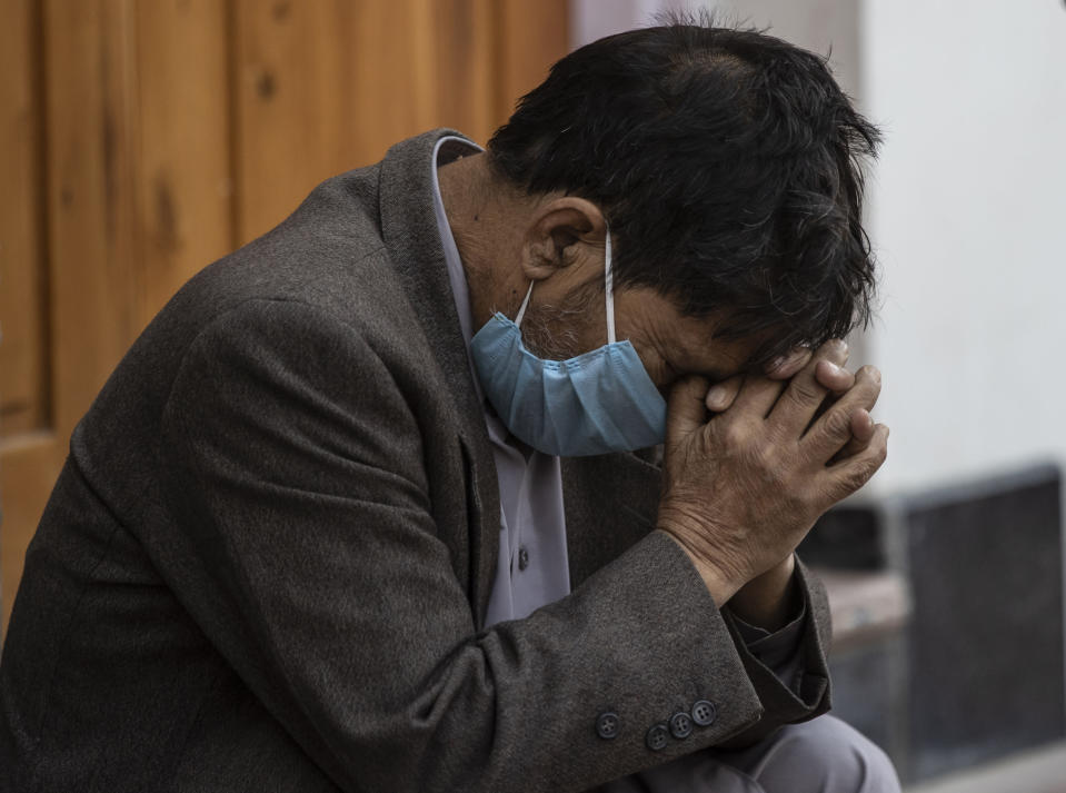 A Kashmiri man sit outside a COVID-19 centre in Srinagar, Indian-controlled Kashmir, Saturday, Oct. 3, 2020. India has crossed 100,000 confirmed COVID-19 deaths on Saturday, putting the country's toll at nearly 10% of the global fatalities and behind only the United States and Brazil. (AP Photo/Mukhtar Khan)