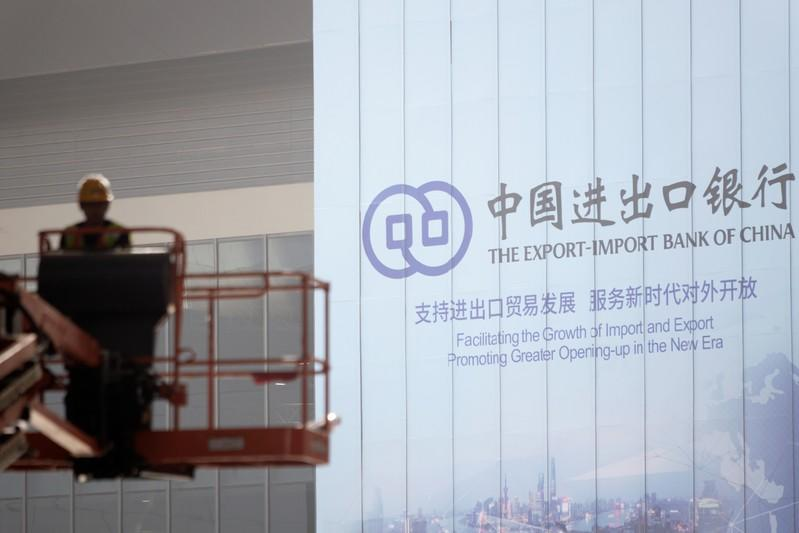 Worker is seen near a sign of the EXIM Bank at the venue for the second China International Import Expo (CIIE) in Shanghai