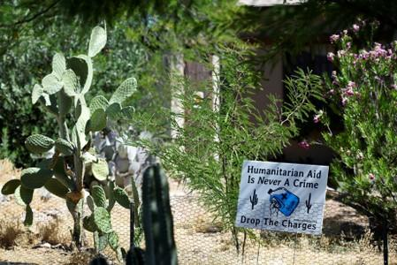 """FILE PHOTO: A sign in support of """"No Más Muertes/No More Deaths"""" is displayed in the neighborhood surrounding the courthouse in Tucson, Arizona where humanitarian volunteer Scott Warren faces charges of harboring and conspiracy to transport undocumented m"""