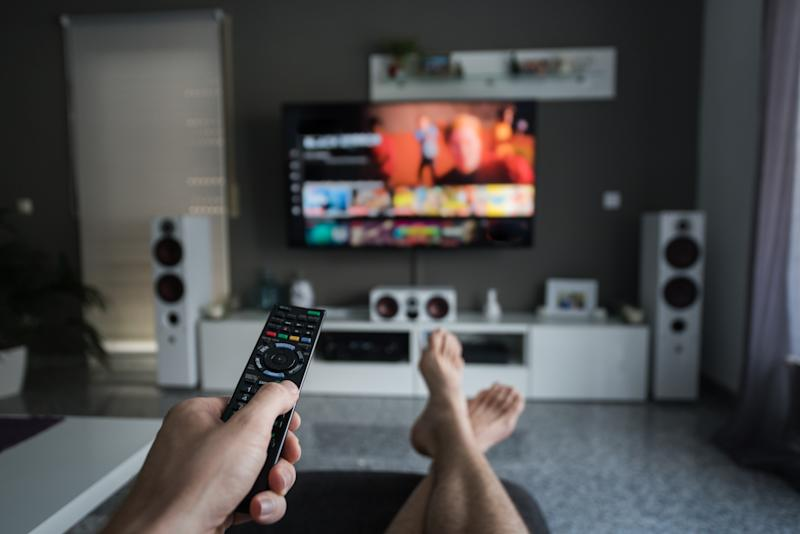 A young man is browsing through television channels with a remote control.