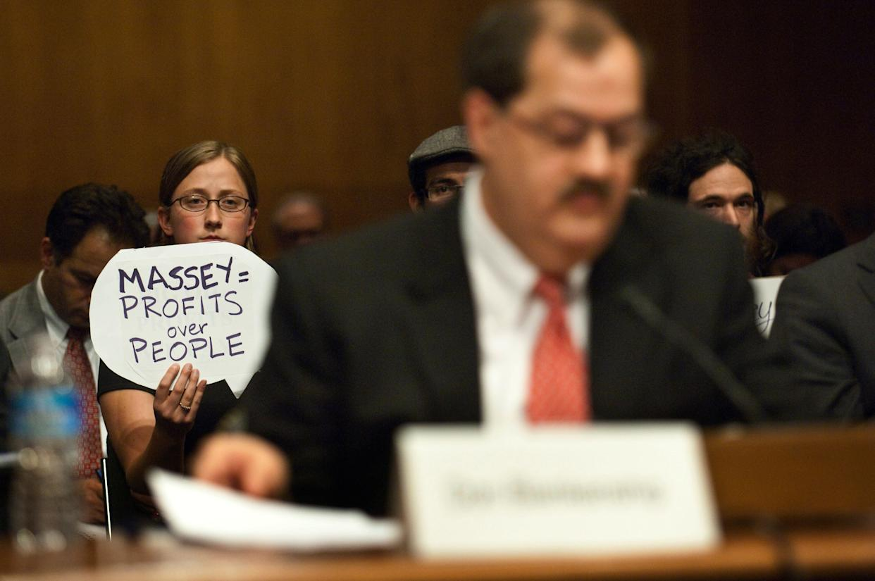 A protester holds a sign behind Don Blankenship, who had been chairman and CEO of Massey Energy Co. until a deadly explosion at one of his mines killed 29 people. (Photo: Scott J. Ferrell via Getty Images)
