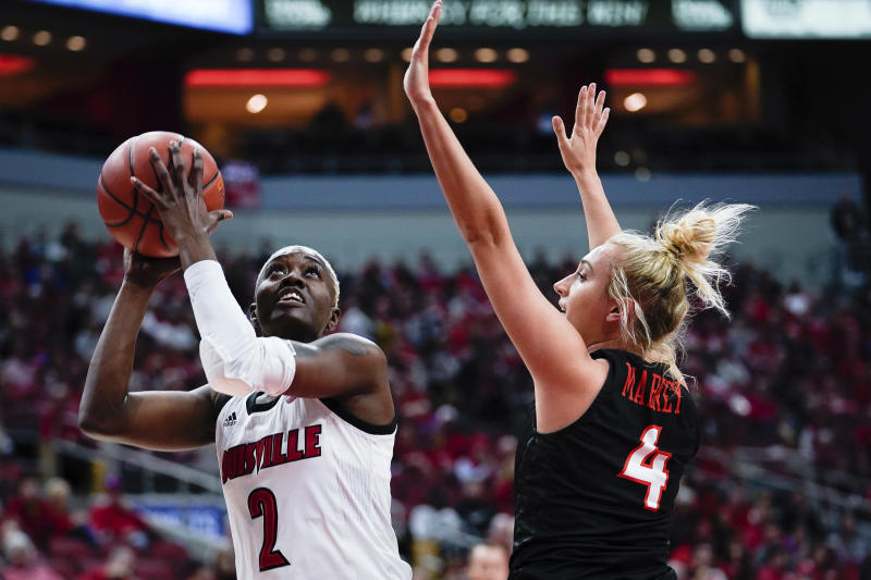 Louisville guard Yacine Diop (2) shoots the ball against Virginia Tech guard Dara Mabrey (4) during the first half of a women's NCAA college basketball game, Sunday, March 1, 2020, at the KFC YUM Center in Louisville, Ky. (AP Photo/Bryan Woolston)