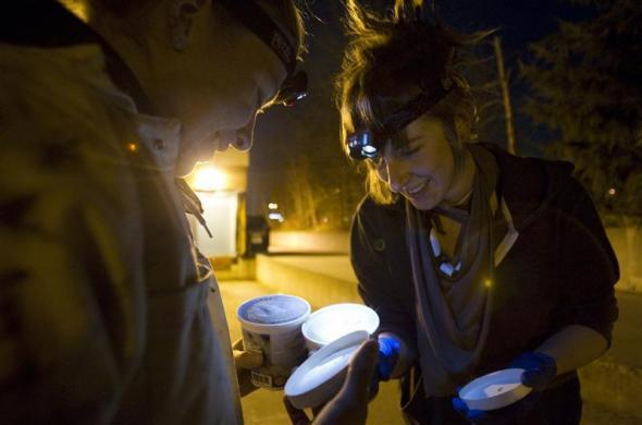 Anna-Rae Douglass (L), 23, and Robin Pickell, practicing 'freegans' inspect cashew ice-cream in a dumpster behind an organic grocery store in Coquitlam, British Columbia April 5, 2012.
