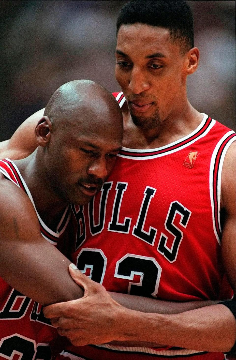 """Scottie Pippen, right, embraces an exhausted Michael Jordan following the Chicago Bulls' win in the """"Flu Game"""" -- Game 5 of the 1997 NBA Finals against the Utah Jazz."""