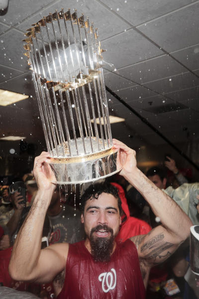 Washington Nationals third baseman Anthony Rendon celebrates with the trophy in the locker room after Game 7 of the baseball World Series against the Houston Astros Wednesday, Oct. 30, 2019, in Houston. The Nationals won 6-2 to win the series. (AP Photo/David J. Phillip)