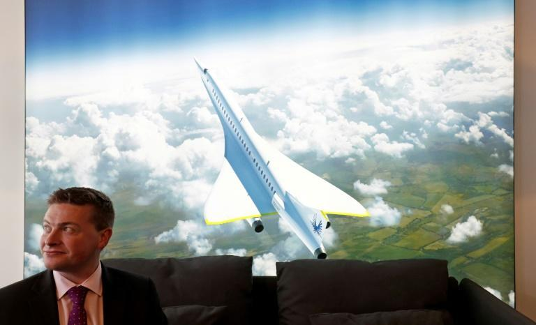Boom Supersonic co-founder Blake Scholl is shown in 2018 in front of an artists impression of his company's proposed design for a supersonic aircraft