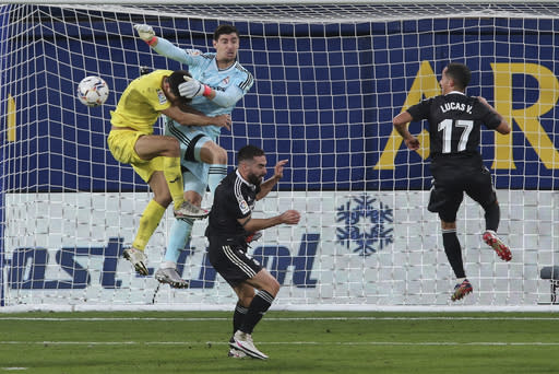 Real Madrid's goalkeeper Thibaut Courtois saves the ball ahead of Villareal's Gerard Moreno during the Spanish La Liga soccer match between Villarreal and Real Madrid in Ceramica stadium in Villarreal, Spain, Saturday Nov. 21, 2020. (AP Photo/Alberto Saiz)