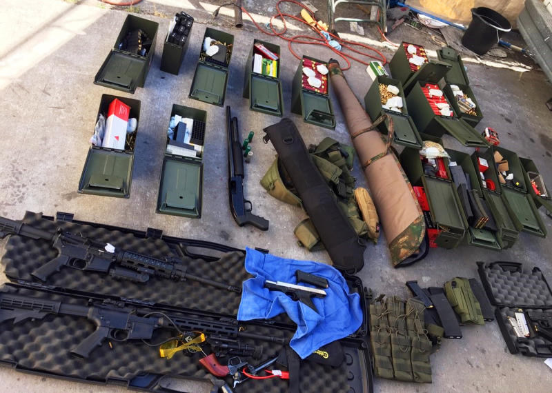 FILE - This undated file photo released Wednesday, Aug. 21, 2019 by the Long Beach, Calif., Police Department shows weapons and ammunition seized from a cook at a Los Angeles-area hotel who allegedly threatened a mass shooting.  There's been a big increase in the number of tips to U.S. law enforcement about potential mass shootings following the three shootings in August that killed 34 people. Experts say media coverage of the shootings makes the public more prone to inform on worrisome relatives or neighbors in attempts to prevent more shootings. Following the high-profile shootings in California and Texas and Ohio, tips to the FBI rose by about 15,000 each week. (Long Beach Police Department via AP, File)