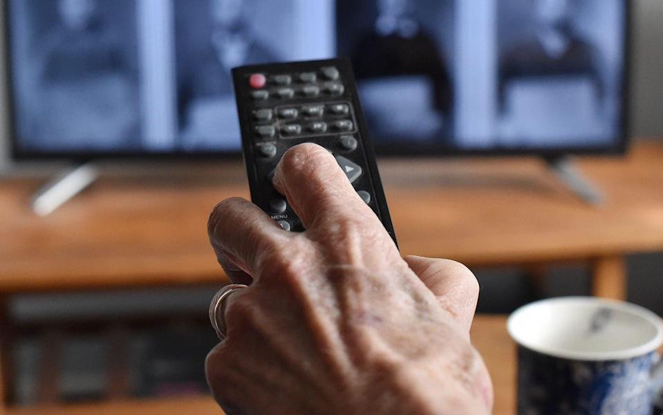 An elderly person's hand and a TV remote