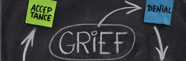 the 5 stages of grief (denial, anger, bargaining, depression, acceptance) written on a chalkboard