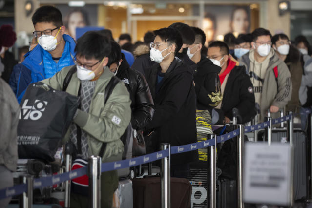 Travellers wearing face masks line up at the Air China check-in counters at Beijing Capital International Airport in Beijing. (AP)