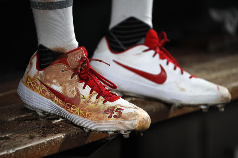 Cleats belonging to St. Louis Cardinals starting pitcher Jack Flaherty are seen as he sits in the dugout during the sixth inning of the team's baseball game against the Colorado Rockies on Friday, Aug. 23, 2019, in St. Louis. (AP Photo/Jeff Roberson)