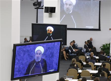 Iran's President Hassan Rouhani is shown on video monitors as he addresses the 68th United Nations General Assembly at UN headquarters in New York, September 24, 2013. REUTERS/Ray Stubblebine