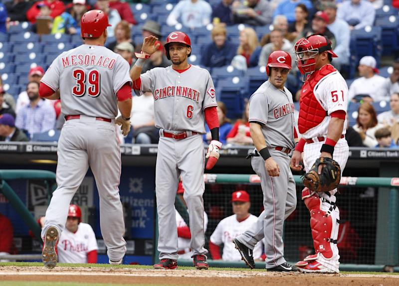 Cincinnati Reds' Devin Mesoraco, left, comes home after hitting a three-run home run scoring, Billy Hamilton, center left, and Skip Schumaker, center right, as Philadelphia Phillies' Carlos Ruiz, right, watches during the first inning of a baseball game, Friday, May 16, 2014, in Philadelphia. (AP Photo/Chris Szagola)