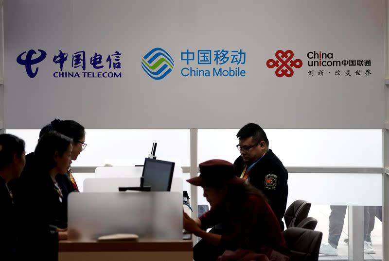 FILE PHOTO: Signs of China Telecom, China Mobile and China Unicom are seen during the China International Import Expo at the National Exhibition and Convention Center in Shanghai