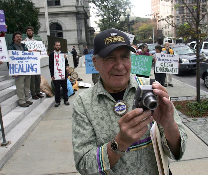 FILE - This Oct. 11, 2007 file photo shows Oren Lyons of the Onondaga Council of Chiefs taking photos outside the federal courthouse in Albany, N.Y., after arguments were heard in the Onondaga Indian Nation's land claim case against New York state. A Native American nation is asking the international community to charge the United States with human rights violations in hopes of getting help with a land claim. The Onondaga Indian Nation says it plans to file a petition at the Organization of American States on Tuesday, seeking human rights violations against the United States government. They want the Inter-American Commission on Human Rights to declare that the U.S. government's decision not to hear their lawsuit asking for the return of 2.5 million acres in upstate New York to be violations of international human rights agreements. (AP Photo/Mike Groll, File)