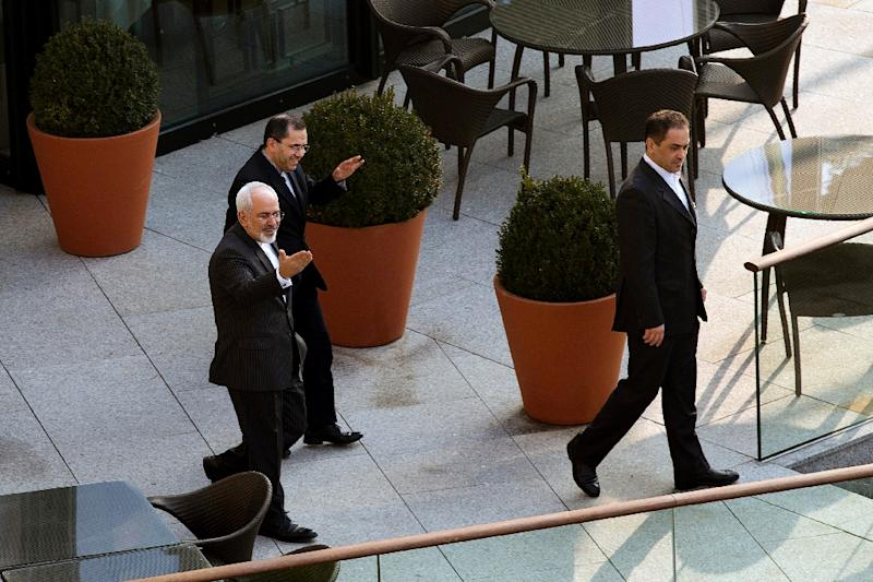 Iran's Foreign Minister Javad Zarif (L) heads out for a walk before a negotiating session with US Secretary of State John Kerry in Lausanne, Switzerland, on March 20, 2015 (AFP Photo/Brian Snyder)