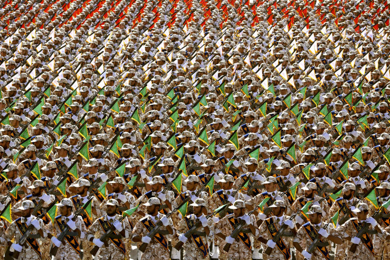 "FILE - In this Sept. 22, 2014 file photo, members of the Iran's Revolutionary Guard march during an annual military parade at the mausoleum of Ayatollah Khomeini, outside Tehran, Iran. On Monday, April 8, 2019, the Trump administration designated Iran's Revolutionary Guard a ""foreign terrorist organization"" in an unprecedented move against a national armed force. Iran's Revolutionary Guard Corps went from being a domestic security force with origins in the 1979 Islamic Revolution to a transnational fighting force. (AP Photo/Ebrahim Noroozi, File)"