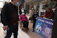 A woman in a wheel chair is pushed past a stand promoting Chinese coronavirus vaccines in Beijing Friday, April 9, 2021. In a rare admission of the weakness of Chinese coronavirus vaccines, the country's top disease control official says their effectiveness is low and the government is considering mixing them to give them a boost. (AP Photo/Ng Han Guan)