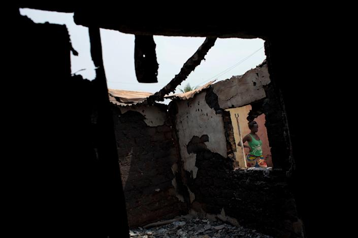 A woman walks past a home that local residents alleged was destroyed by a rocket during a Wednesday attack by Chadian peacekeepers, in the Gobongo neighborhood of Bangui, Central African Republic, Thursday, Dec. 26, 2013. Residents and anti-balaka militiamen claimed the neighborhood had been attacked by Chadian soldiers, and that anti-balaka militiamen had retaliated by destroying a pick-up truck carrying soldiers with a grenade. Their account could not be independently verified. Several nearby homes and shops were destroyed. The spokesman for an African Union peacekeeping force says six Chadian peacekeepers were killed and 15 were wounded, after being attacked Wednesday. The Chadian contingent, which is made up of Arabic-speaking Muslim soldiers, has been accused of taking sides against the Christian population in the country's sectarian conflict. (AP Photo/Rebecca Blackwell)