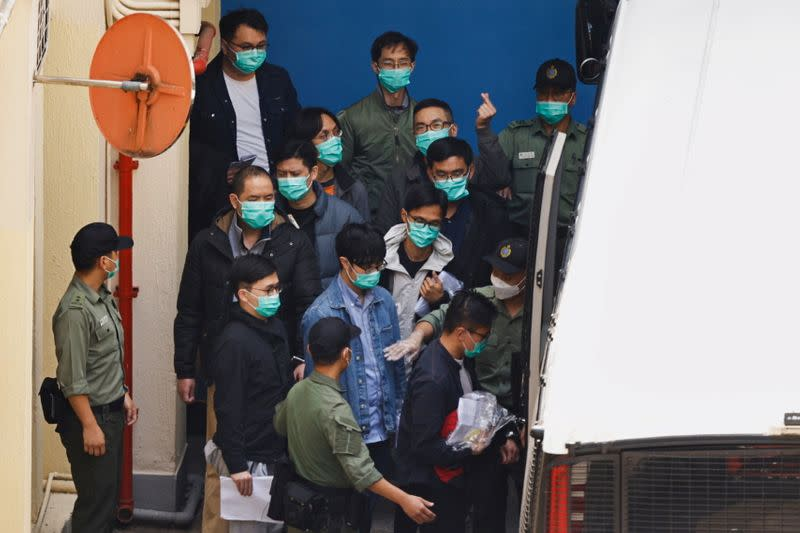 Pro-democracy activists including Alvin Yeung, Eddie Chu and Jeremy Tam walk to a prison van to head to court, over national security law charges, in Hong Kong
