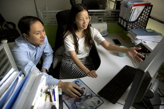 He Jiankui, left, and Zhou Xiaoqin work a computer at a laboratory in Shenzhen in southern China