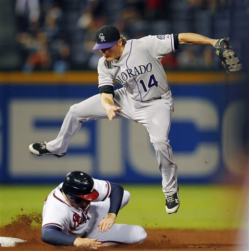 Colorado Rockies shortstop Josh Rutledge (14) avoids Atlanta Braves' Freddie Freeman (5) as he tries to turn a double play on a ground ball from Brian McCann in the fourth inning of a baseball game, Wednesday, Sept. 5, 2012, in Atlanta,. Rutledge's throw to first was wild, allowing a run to score and McCann to advance to second base. (AP Photo/John Bazemore)